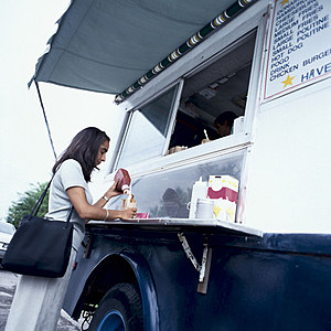 Woman with French fries and ketchup at food truck